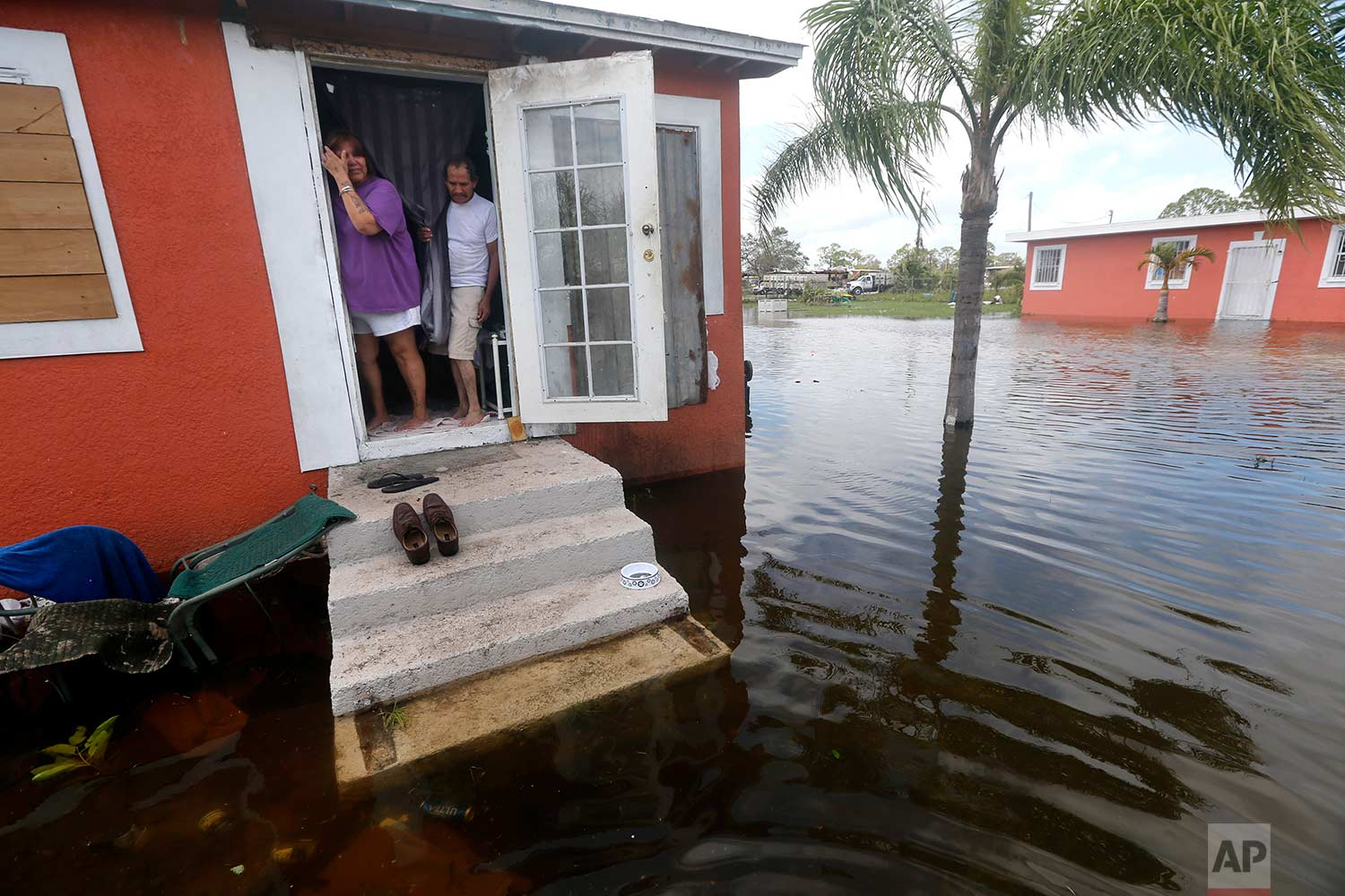 In this Sept. 11, 2017 file photo, Quintana and Liz Perez look at the flooding outside their home in the aftermath of Hurricane Irma, in Immokalee, Fla, one of the poorest towns in the state. Home of many day laborers and migrant workers, Immokalee sustained heavy damage from Irma that will take months to overcome. (AP Photo/Gerald Herbert)