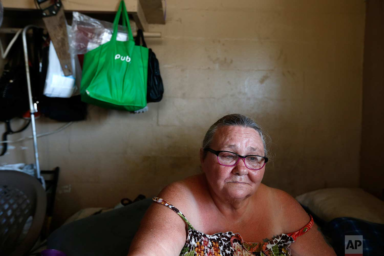 In this Sept. 12, 2017 photo, Pattie Deeley, who has asthma and other health problems which keep her on supplemental oxygen, sits in her small cinderblock apartment during a multi-day power failure in the aftermath of Hurricane Irma, in Immokalee, Fla. Unable to cook after the storm, Deeley said she had to spend extra money buying meals after Irma. (AP Photo/Gerald Herbert)