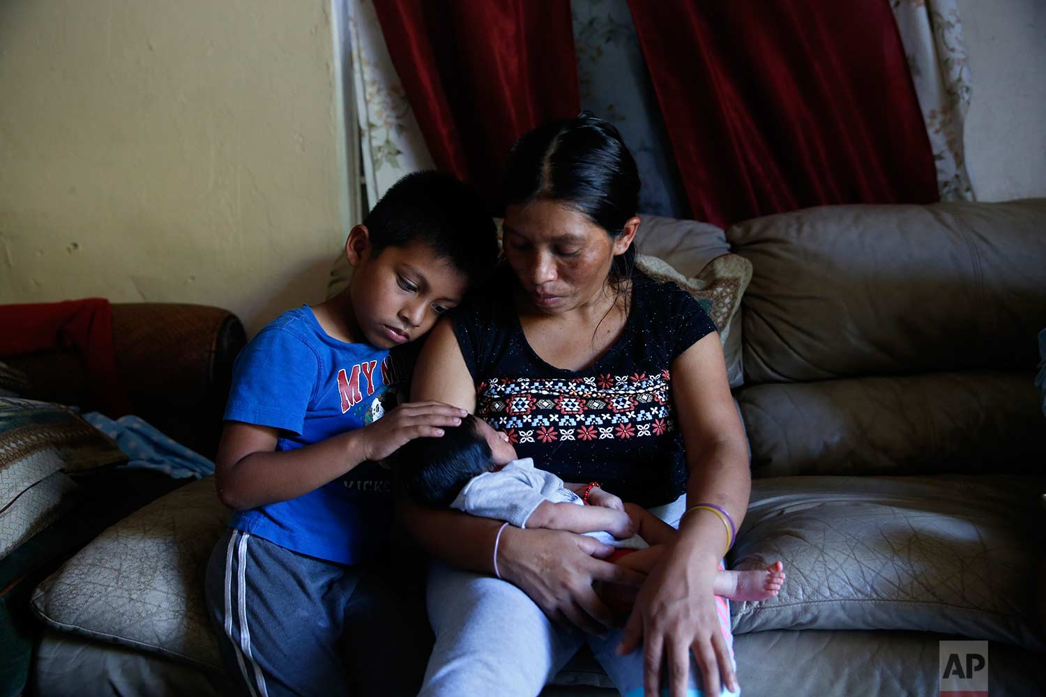 In this Sept. 12, 2017 photo, Aura Gaspar sits with her two-week old baby Ashley, and her son, Isaac, 5, in their home, dark due to a power failure from Hurricane Irma, in Immokalee, Fla. Gaspar said they spent $600 getting ready for Irma, the equivalent of two weeks pay. (AP Photo/Gerald Herbert)
