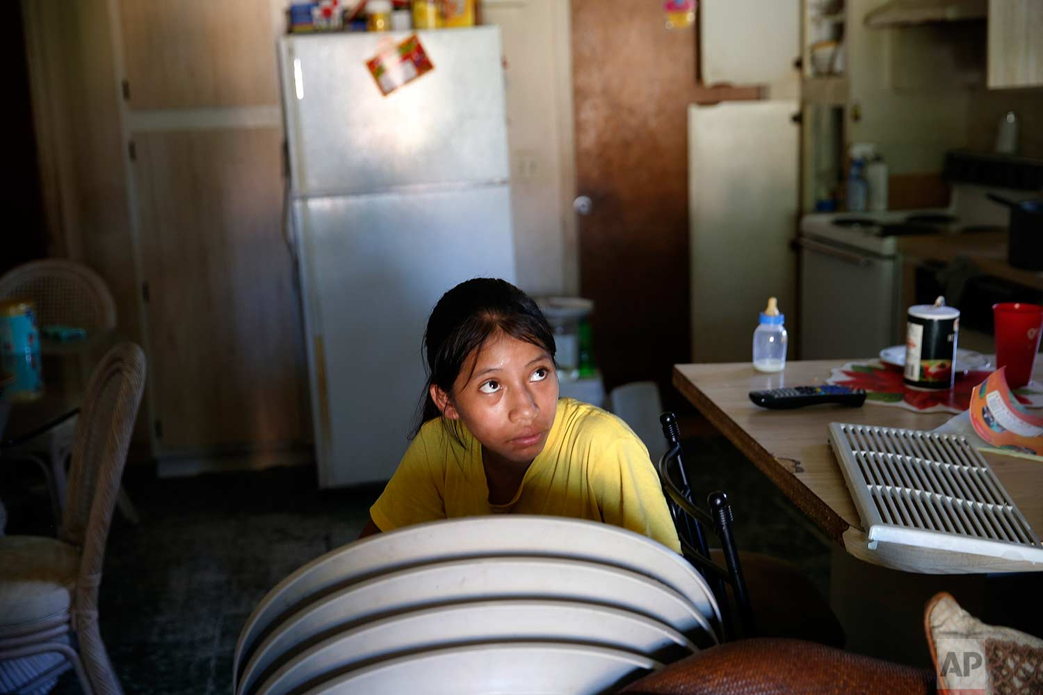 In this Sept. 12, 2017 photo, Andrea Sevation sits in her family home, with the front open for light due to losing power from Hurricane Irma, in Immokalee, Fla. Her father spent $600 getting ready for the storm, the equivalent of two weeks pay. (AP Photo/Gerald Herbert)
