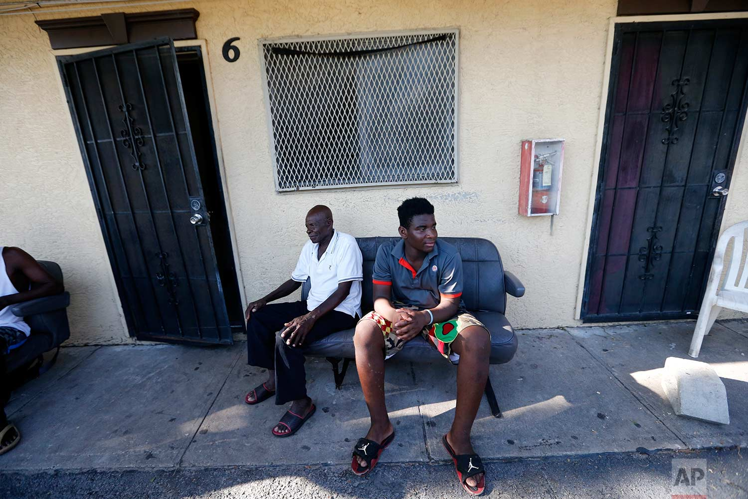 In this Sept. 12, 2017 photo, Woodchy Darius, right, sits outside the small cinderblock apartment he lives in, in the aftermath of Hurricane Irma, in Immokalee, Fla. A Haitian immigrant, he is trying to decide to go to school next week, or work in the fields to make up for lost income due to the storm. (AP Photo/Gerald Herbert)