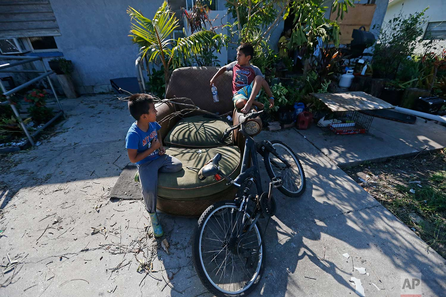 In this Sept. 12, 2017 photo, Giovani Gaspar, 6, right, and his brother, Isaac, 5, play on a chair outside their home, in the aftermath of Hurricane Irma, in Immokalee, Fla. Their father spent $600 getting ready for Irma, the equivalent of two weeks pay. (AP Photo/Gerald Herbert)