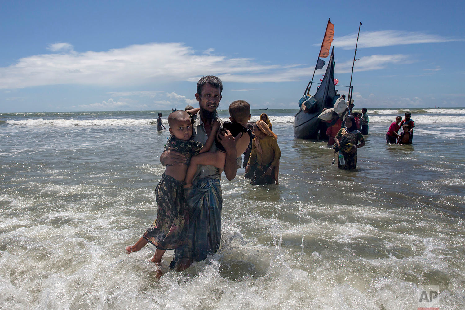 A Rohingya Muslim man walks to shore carrying two children after they arrived on a boat from Myanmar to Bangladesh in Shah Porir Dwip, Bangladesh, Thursday, Sept. 14, 2017. Those who arrived Wednesday in wooden boats described ongoing violence in Myanmar, where smoke could be seen billowing from a burning village, suggesting more Rohingya homes had been set alight. (AP Photo/Dar Yasin)