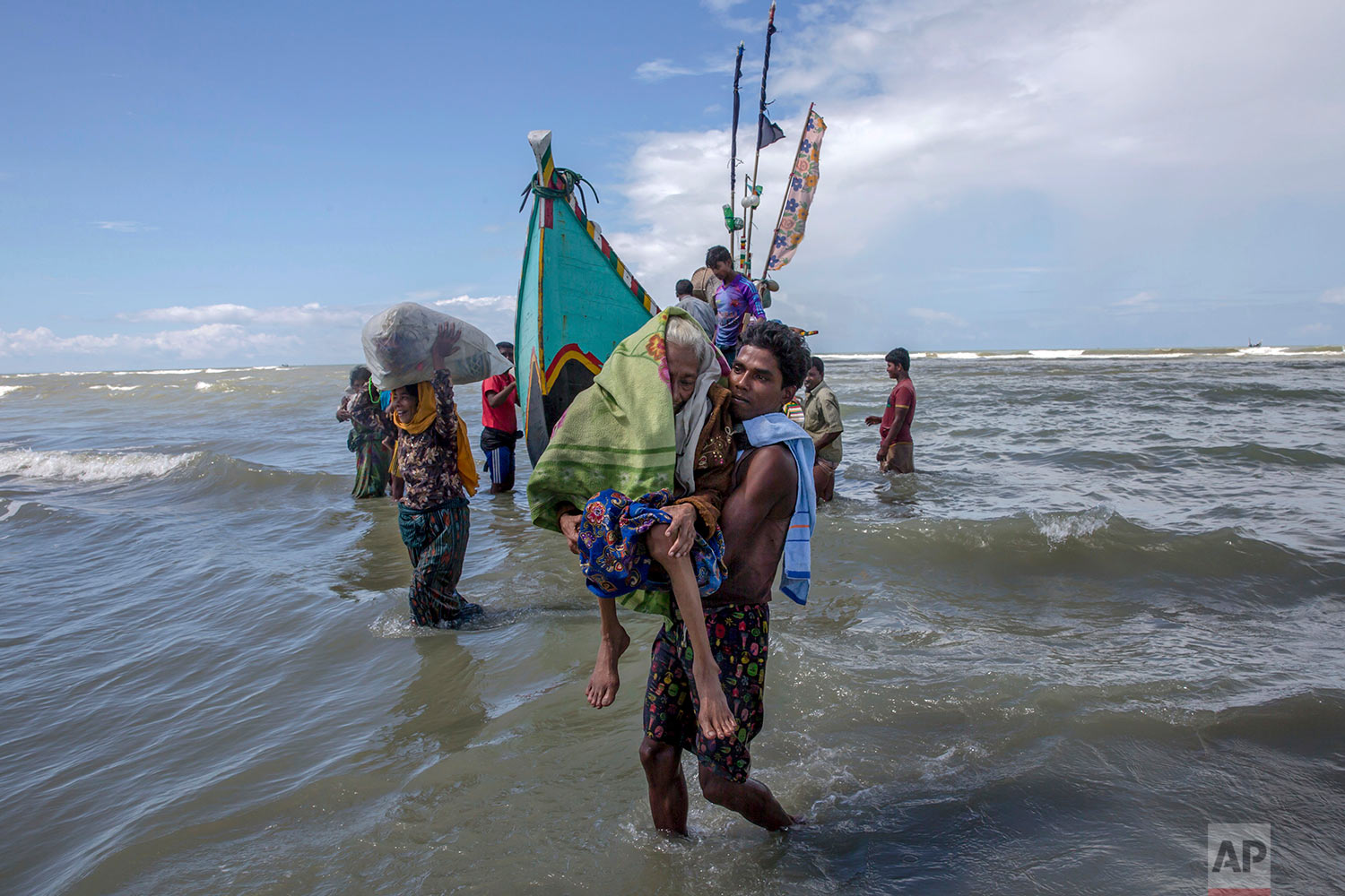 A Rohingya Muslim man walks to shore carrying an elderly woman after they arrived on a boat from Myanmar to Bangladesh in Shah Porir Dwip, Bangladesh, Thursday, Sept. 14, 2017. Nearly three weeks into a mass exodus of Rohingya fleeing violence in Myanmar, thousands were still flooding across the border Thursday in search of help and safety in teeming refugee settlements in Bangladesh. (AP Photo/Dar Yasin)