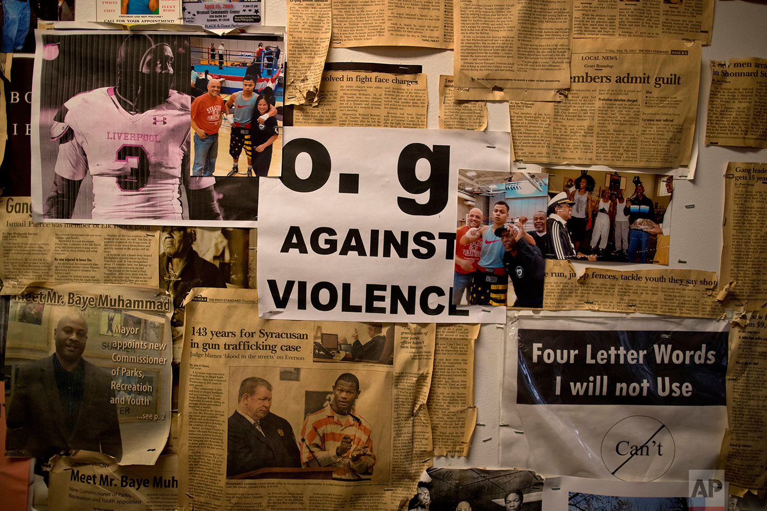 A flyer created by Old Gangsters Against Violence hangs on a wall with newspaper and magazine clippings at the Faith and Hope Community Center, Monday, Aug. 21, 2017, in Syracuse, N.Y. (AP Photo/Julie Jacobson)