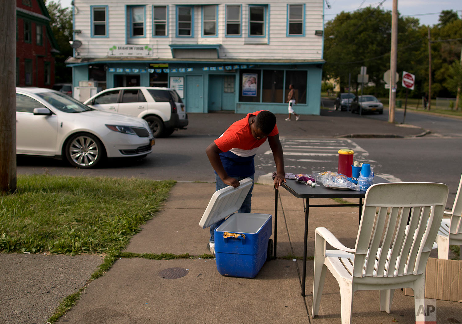 Deivion Rohdafox checks a cooler he and his brother and cousins were using to sell snacks, soda and sweetened drinks on a street corner of their South Side neighborhood, Monday, Aug. 21, 2017, in Syracuse, N.Y. The 11-year-old was hoping to use the money to buy school supplies. Syracuse, on the eastern fringe of upstate New York's Finger Lakes region, has struggled to find its footing since factories making air conditioners and auto parts shut down. (AP Photo/Julie Jacobson)