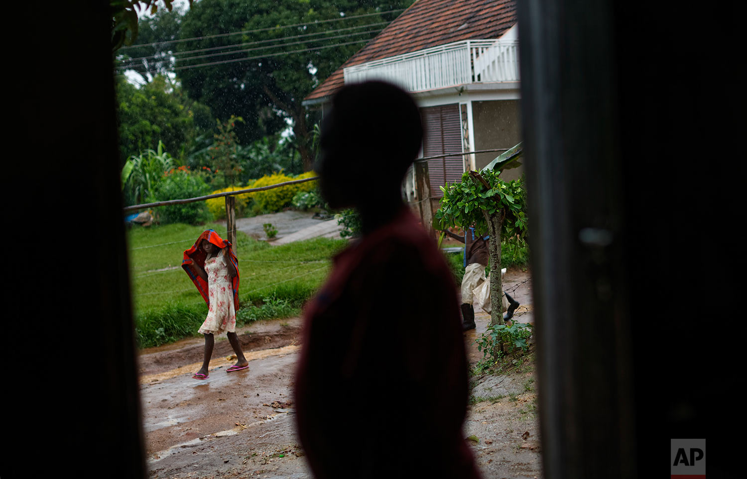 In this Tuesday, May 30, 2017 photo, a pregnant 15-year-old girl who was the victim of statutory rape, stands in a doorway of the house where she stays in Masaka, Uganda.(AP Photo/Ben Curtis)