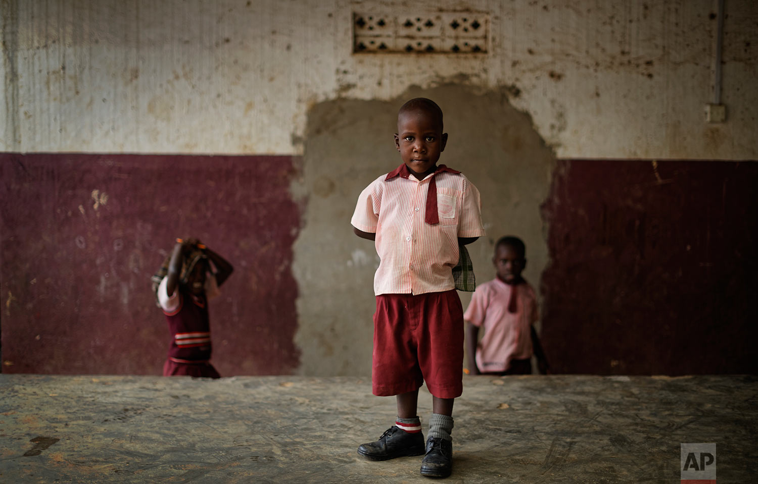In this Tuesday, May 30, 2017 photo, Keron Sembuya, who teachers believe to be around 4 or 5 years old, stands for a photograph at the Mpugwe Parents Junior School which he attends in Masaka, Uganda. (AP Photo/Ben Curtis)