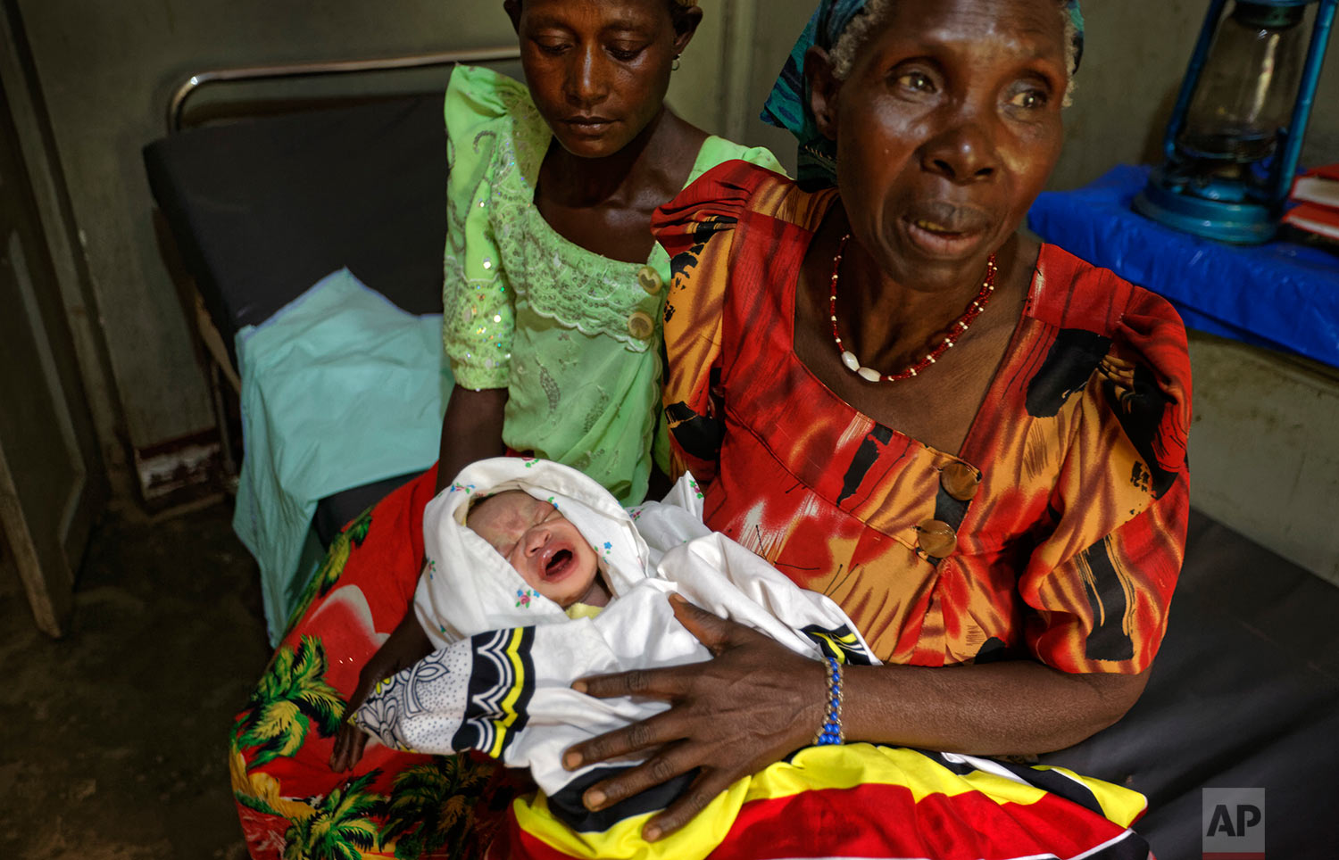 In this Wednesday, May 31, 2017 photo, grandmother Mauda Byarugaba, right, holds her grandson Ben Ssekalunga, who was passed to her by a midwife moments after his birth, as she sits next to an unidentified friend in the maternity room of a health clinic with no running water in Lwamaggwa, near Masaka, in Uganda. A census worker recorded Ben's details in a birth register shortly after delivery. (AP Photo/Ben Curtis)