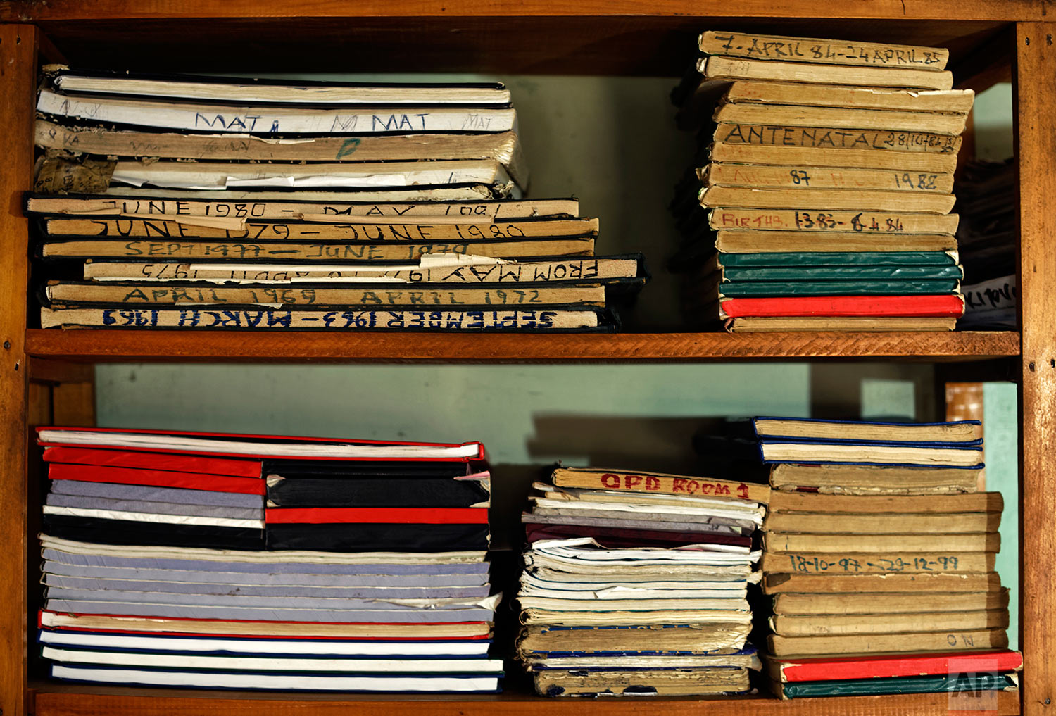 In this Tuesday, May 30, 2017 photo, old archives of birth registrations recorded only by hand in books, prior to the introduction of a national computerized register where administrators can enter births over the internet, are stored on shelves at the St. Joseph's Hospital in Kitovu, Uganda. (AP Photo/Ben Curtis)