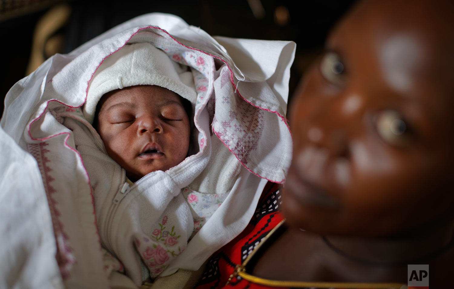 In this Tuesday, May 30, 2017 photo, Mary Nabiryo holds her 1-day-old son, Andrew, in the maternity ward of St. Joseph's Hospital in Kitovu, Uganda. The birth registration campaign in Uganda dates back only about five years and there's still uncertainty as to whether the government will invest sufficient funds to expand and sustain it. (AP Photo/Ben Curtis)