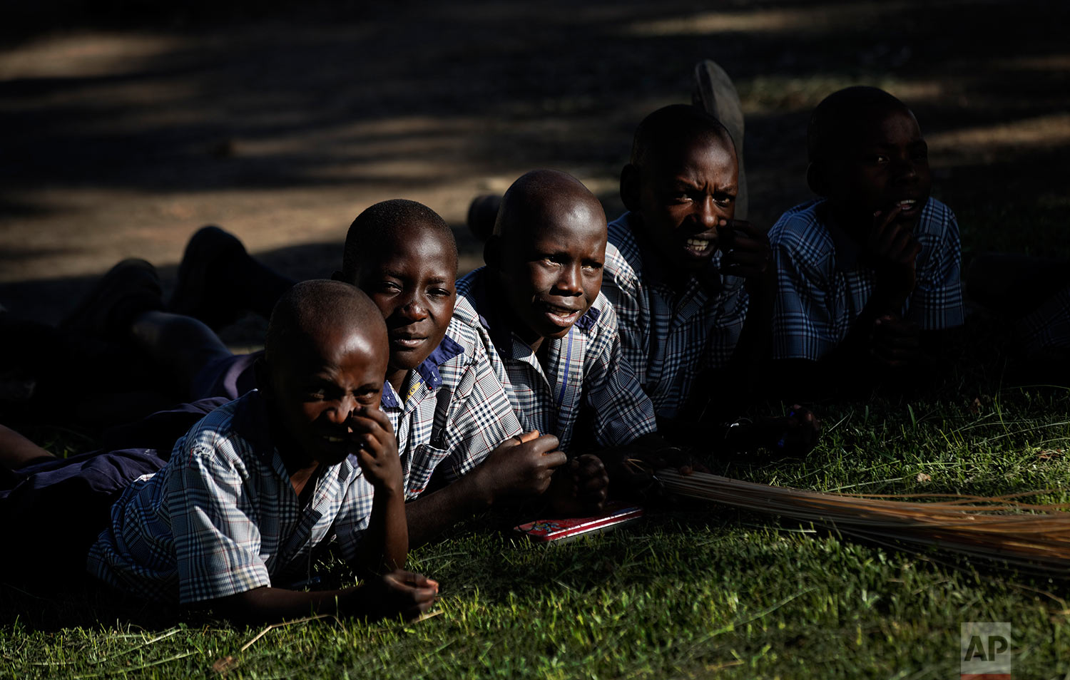 In this Wednesday, May 31, 2017 photo, children lie on the grass during break at the Side-By-Side Boetheo School, which assists mostly orphans who were previously out of school but now receive scholarship aid from a donor if they satisfy criteria such as having a birth certificate, in Rakai, Uganda. (AP Photo/Ben Curtis)