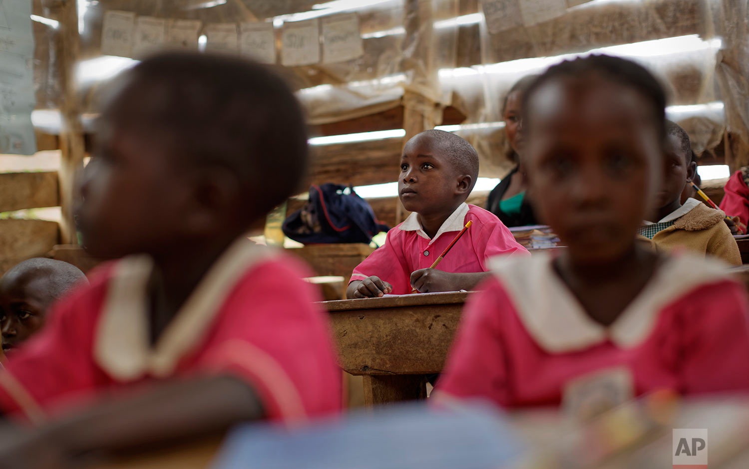 In this Thursday, June 1, 2017 photo, Abdu Kabanda, 6, center, who is HIV-positive and is able to receive treatment from a support group because he is able to show a birth certificate to prove his age, sits in his class at the Jovia nursery and primary school in Kyanangazi village, Uganda. (AP Photo/Ben Curtis)