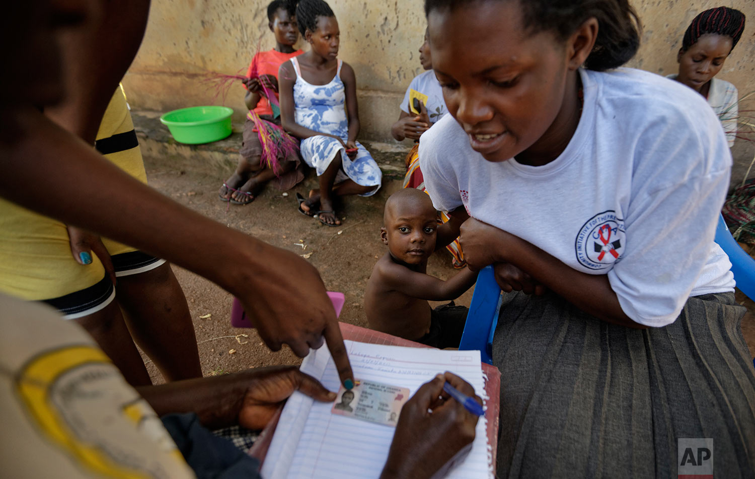 In this Thursday, June 1, 2017 photo, Felista Namotovu, 26, right, gives the details of the birth of her son, Reyman Lubega, 3, center, to health worker Josephine Nakachwa, as Nakachwa goes door-to-door to check if parents have registered the births of their children, in the village of Kifuuta, Uganda. (AP Photo/Ben Curtis)