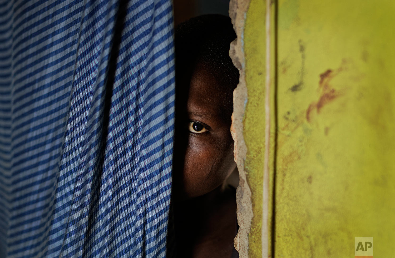 In this Thursday, June 1, 2017 photo, a 15-year-old who was raped when she was 14 talks to a member of UNICEF staff at her home in a village near Masaka, Uganda. The man who raped her was remanded to jail pending trial after an aid worker assisted her father in obtaining a birth certificate to prove she was under 18, a document she did not previously have. (AP Photo/Ben Curtis)