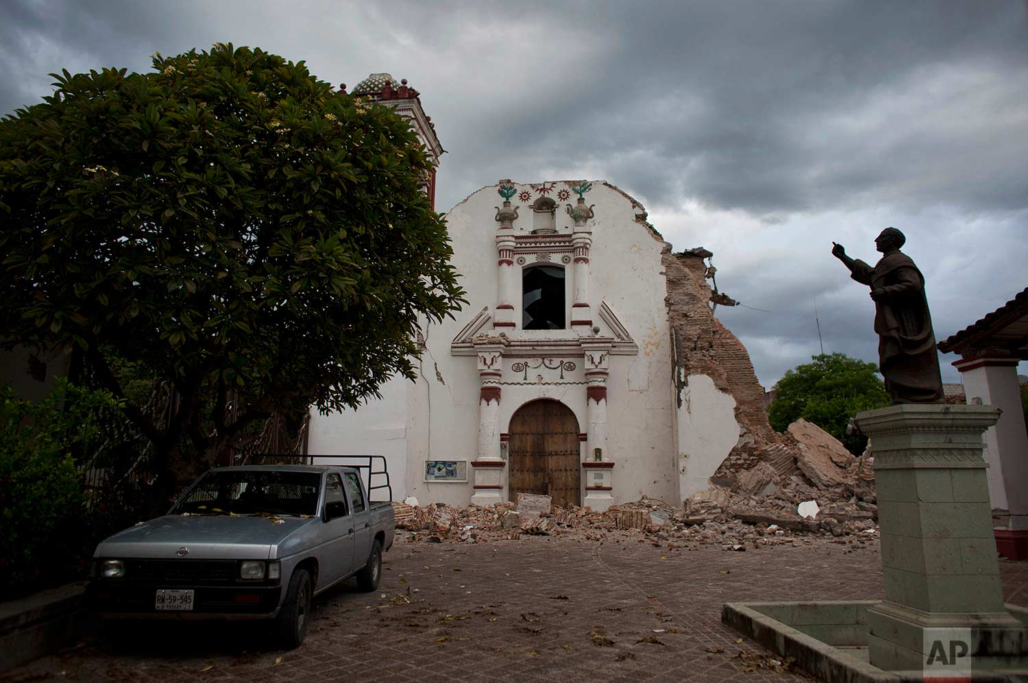 Clouds hover over the damaged San Vicente church on Sunday, Sept. 10, 2017 after an 8.1 magnitude earthquake the previous week in Juchitan, Oaxaca state, Mexico. In Juchitan, a third of the homes are reported uninhabitable and repeated aftershocks have scared people away from many structures still standing. (AP Photo/Rebecca Blackwell)