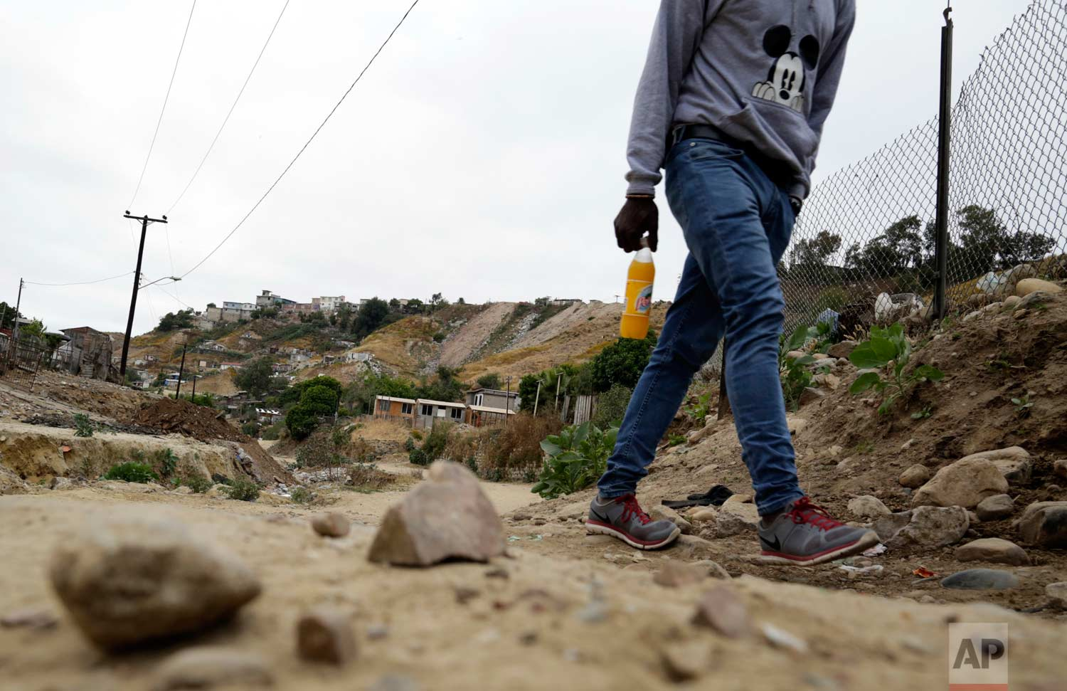In this May 24, 2017 photo, a Haitian man makes his way up a dirt road towards a makeshift shelter at The Ambassadors of Jesus Church in Tijuana, Mexico. (AP Photo/Gregory Bull)