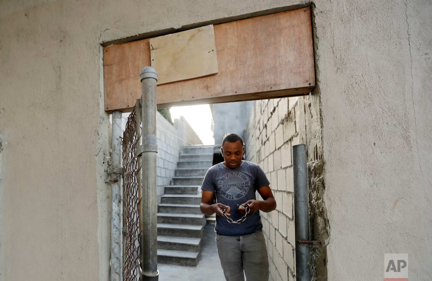 In this June 6, 2017 photo, Abelson Etienne holds the lock to his apartment in Tijuana, Mexico. (AP Photo/Gregory Bull)