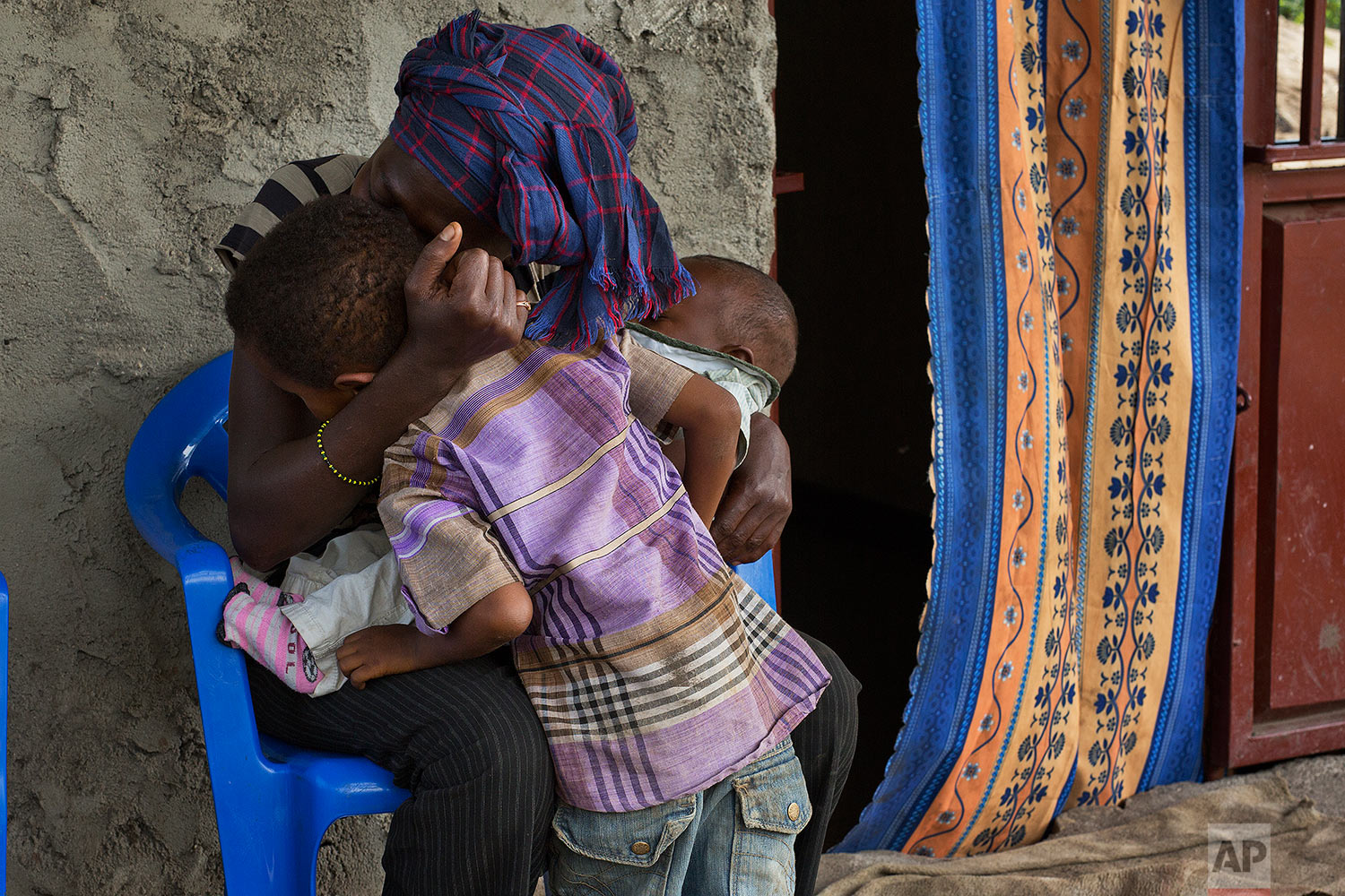 In this photo taken Aug. 11, 2016, 8-year-old Michael is hugged by his mother Blandine at their home in the Congo Ituri province capital Bunia. (AP Photo/Jerome Delay)