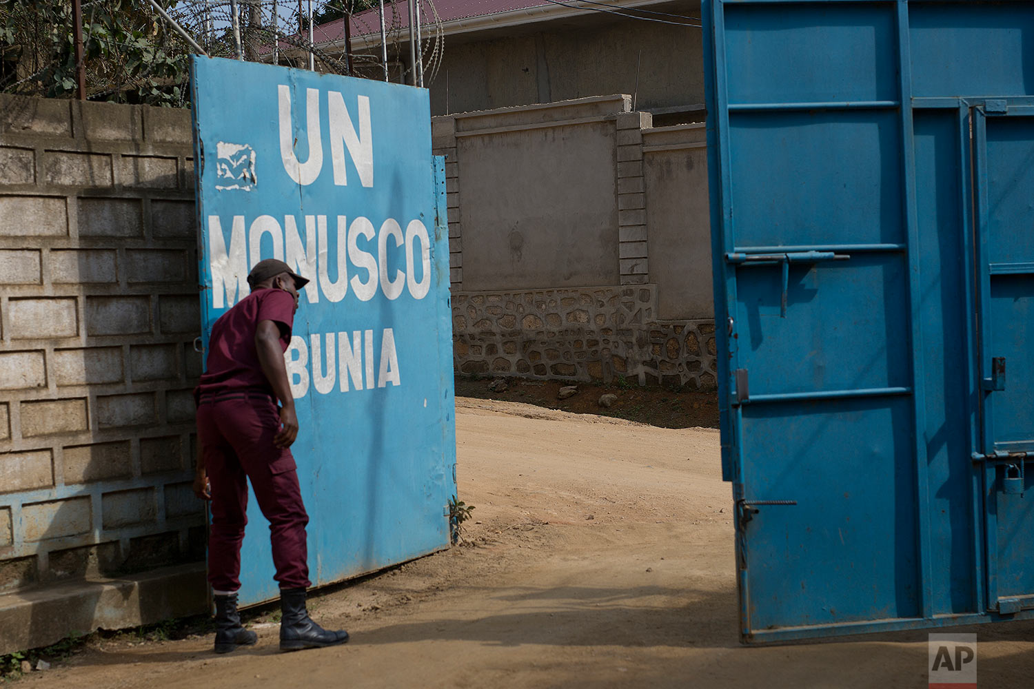 In this photo taken Aug. 11, 2016, a security guard closes the gate of the UN compound in the Congo Ituri province capital Bunia. (AP Photo/Jerome Delay)