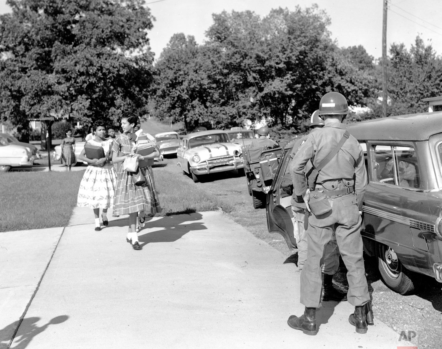 Black students leave the home of Mrs. L.C. Bates, president of the Arkansas NAACP, on the morning of Sept. 25, 1957 to walk toward a station wagon driven by a trooper from the 101st Airborne Division enroute to Central High School. (AP Photo)