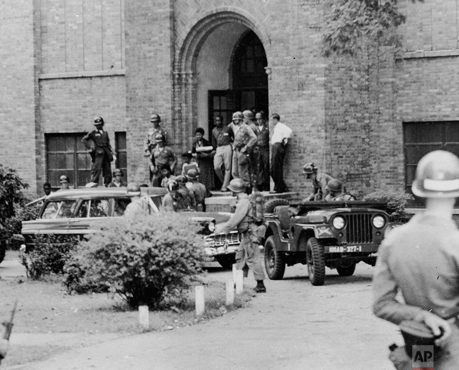 Nine black students leave Central High School in Little Rock, Ark., after classes, Sept. 25, 1957. They are being escorted from a side door by troops of the 101st Airborne Division. (AP Photo)