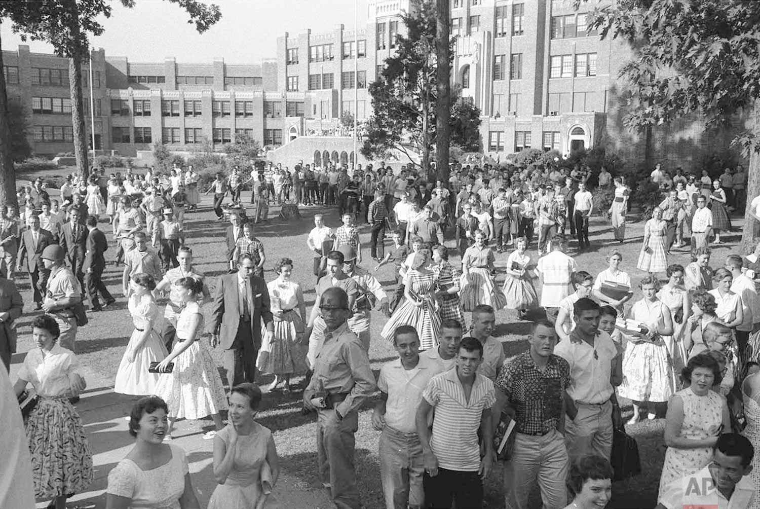 In this Sept. 1957 photo, students are watched by soldiers and reporters as they leave Little Rock's Central High School in Little Rock, Ark.  (AP Photo/Will Counts)