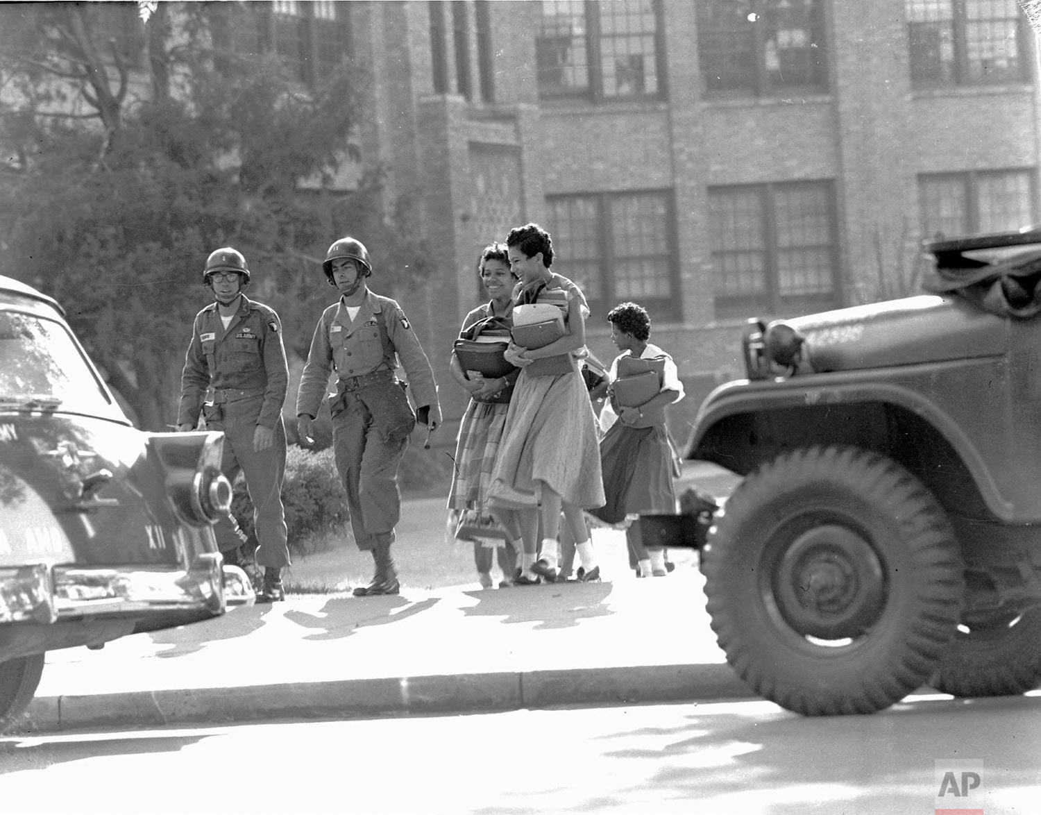 Two paratroop officers escort black students from Central High School in Little Rock, Ark., September 27, 1957.  School was closing for the weekend.  (AP Photo)