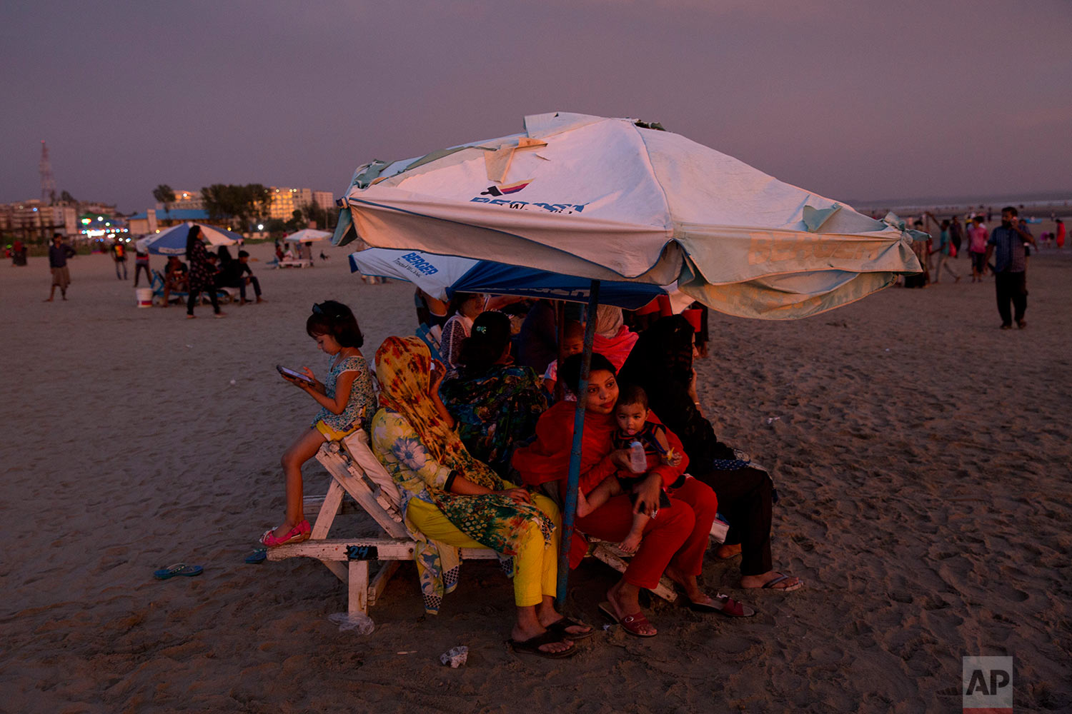 In this Friday, Sept. 22, 2017 photo, a Bangladeshi family enjoys the sunset at Cox's Bazar beach in Bangladesh. (AP Photo/Bernat Armangue)