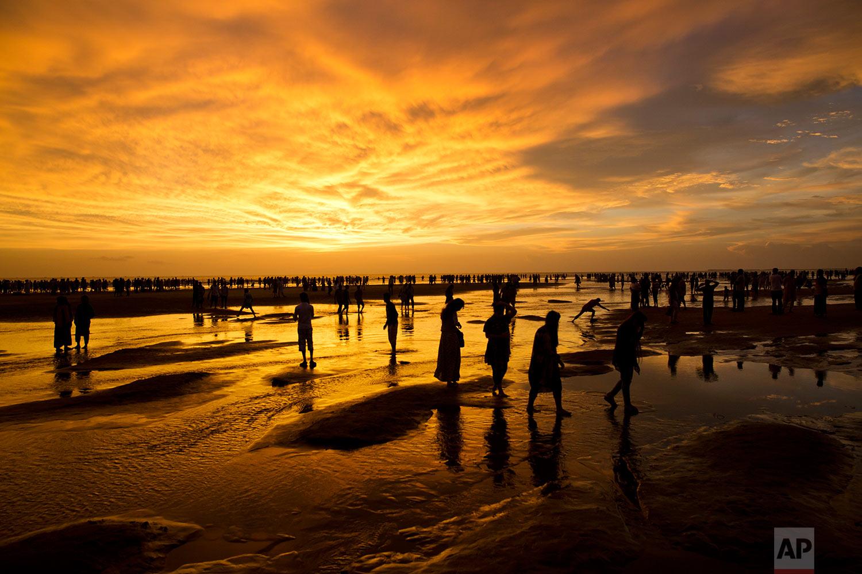 In this Friday, Sept. 22, 2017 photo, Bangladeshis walk on the beach at sunset in Cox's Bazar, Bangladesh. (AP Photo/Bernat Armangue)