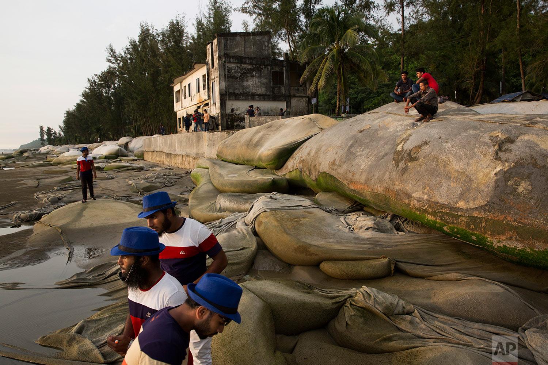 In this Saturday, Sept. 23, 2017 photo, Bangladeshi men sit on an embankment and watch the sun set at a beach in Cox's Bazar area, Bangladesh. (AP Photo/Bernat Armangue)