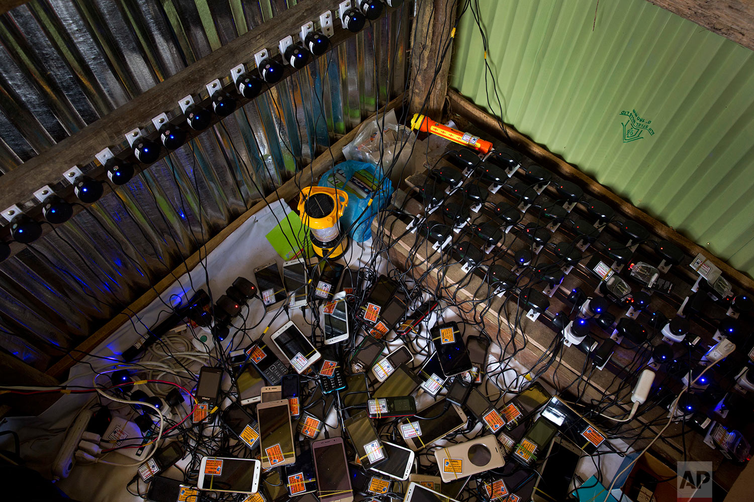 In this Saturday, Sept. 23, 2017 photo, dozens of cellphones charge in a makeshift shop for a price of five taka (US$ 0.06), in Lambashia, near Kutupalong. (AP Photo/Bernat Armangue)