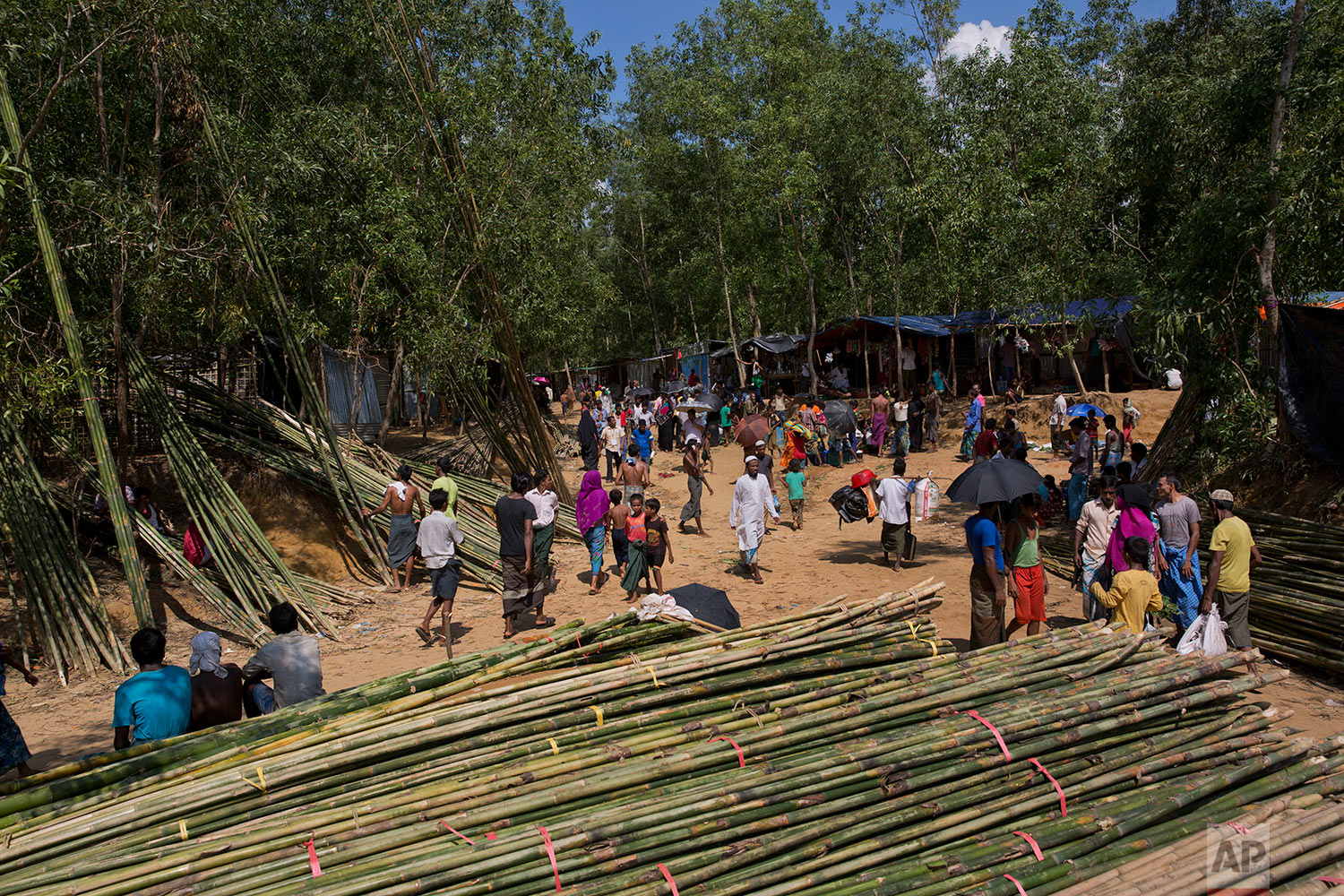 In this Saturday, Sept. 23, 2017 photo, newly arrived Rohingya Muslims walk past bundles of bamboo poles used to make tents at Lambashia, near Kutupalong, Bangladesh. (AP Photo/Bernat Armangue)
