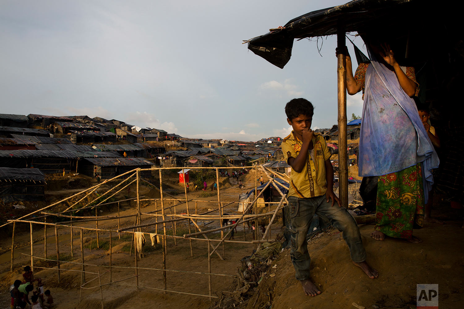 In this Sept. 24, 2017 photo, newly arrived Rohingya Muslims stand next to their new shelters in Balukhali refugee camp, Bangladesh. (AP Photo/Bernat Armangue)