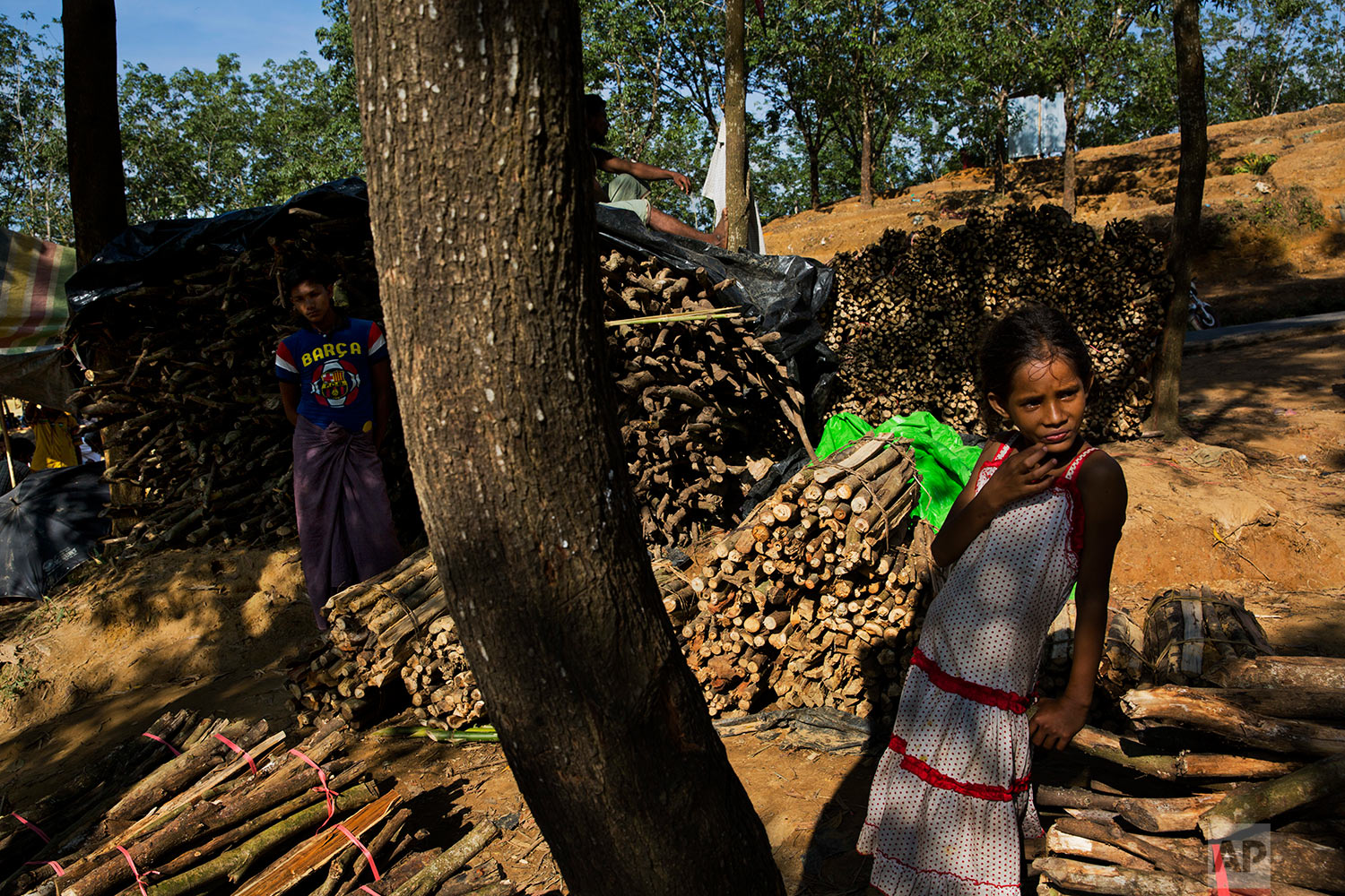 In this Sunday, Sept. 24, 2017 photo, newly arrived Rohingya Muslims sell wood in Kutupalong refugee camp, Bangladesh. (AP Photo/Bernat Armangue)
