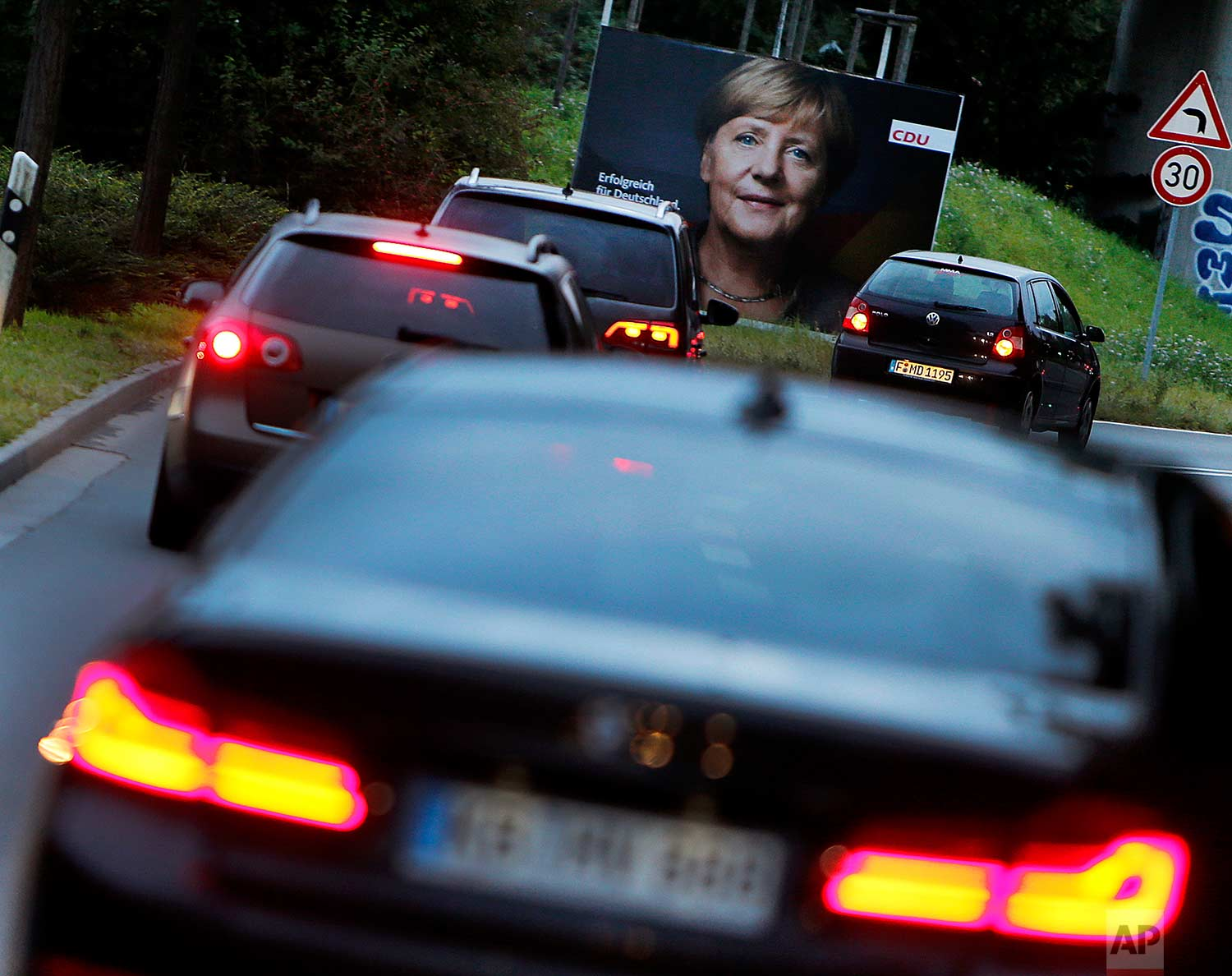 Cars pass an election poster showing German Chancellor Angela Merkel in Frankfurt, Germany, Tuesday, Sept. 19, 2017. (AP Photo/Michael Probst)