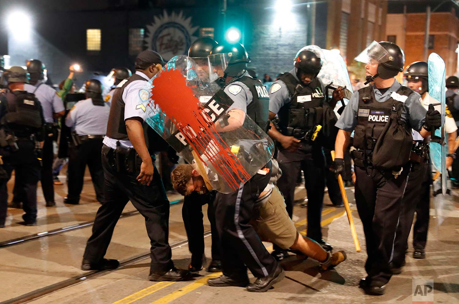 "Police arrest a man as they try to clear a violent crowd Saturday, Sept. 16, 2017, in University City, Mo. Earlier, protesters marched peacefully in response to a not guilty verdict in the trial of former St. Louis police officer Jason Stockley. The American Civil Liberties Union of Missouri filed a lawsuit against the city of St. Louis on Friday over what it called ""unlawful and unconstitutional action"" during demonstrations that followed the acquittal of a white former police officer in the death of a black man. (AP Photo/Jeff Roberson)"