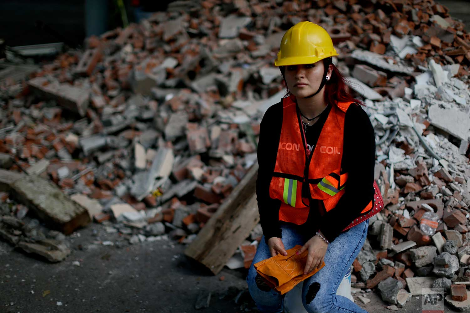 Frida Islas Rueda, 22-year-old student, poses for a picture near debris from a damaged building after an earthquake, Sept. 22, 2017, in Mexico City. (AP Photo/Natacha Pisarenko)
