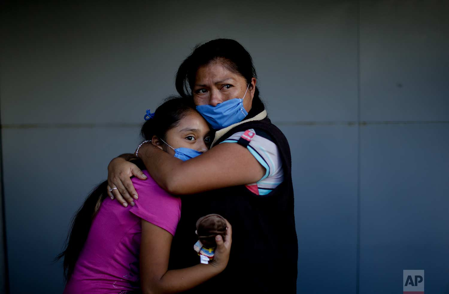 Veronica Aguilar Naranjo embraces her 11-year-old daughter Veronica Villanueva as they look at a collapsed building where people search for survivors, Sept. 22, 2017, after an earthquake in Mexico City. (AP Photo/Natacha Pisarenko)