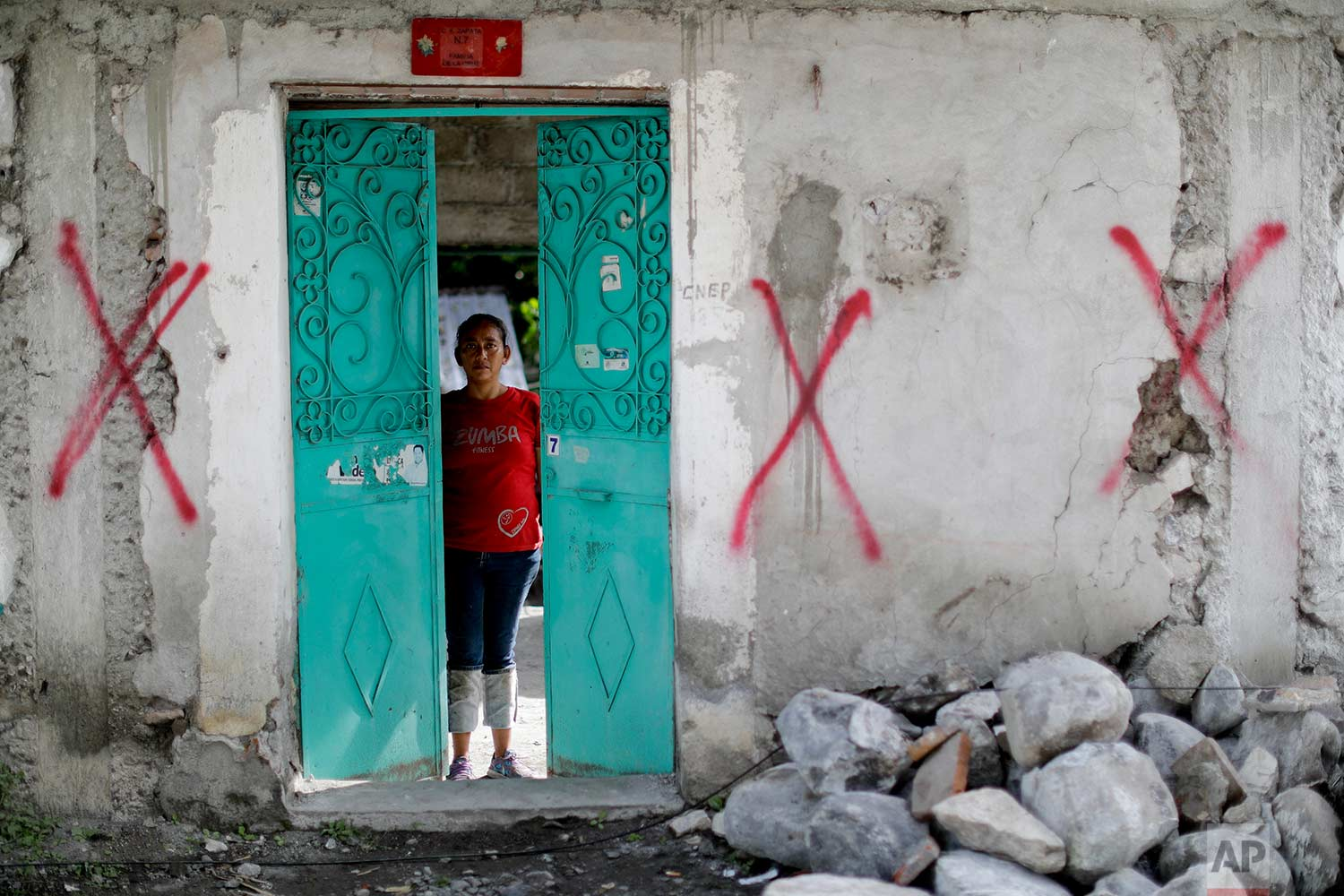 """Nadia Rosas stands inside her aunt's home covered with spray paint symbols designating it condemned, after it was destroyed by an earthquake, Sept. 23, 2017,in Atzala, Mexico. Rosas moved in with her 68-year-old aunt after the earthquake destroyed everything. """"In these catastrophes we're united as brothers, as people, as women,"""" Rosas said. (AP Photo/Natacha Pisarenko)"""