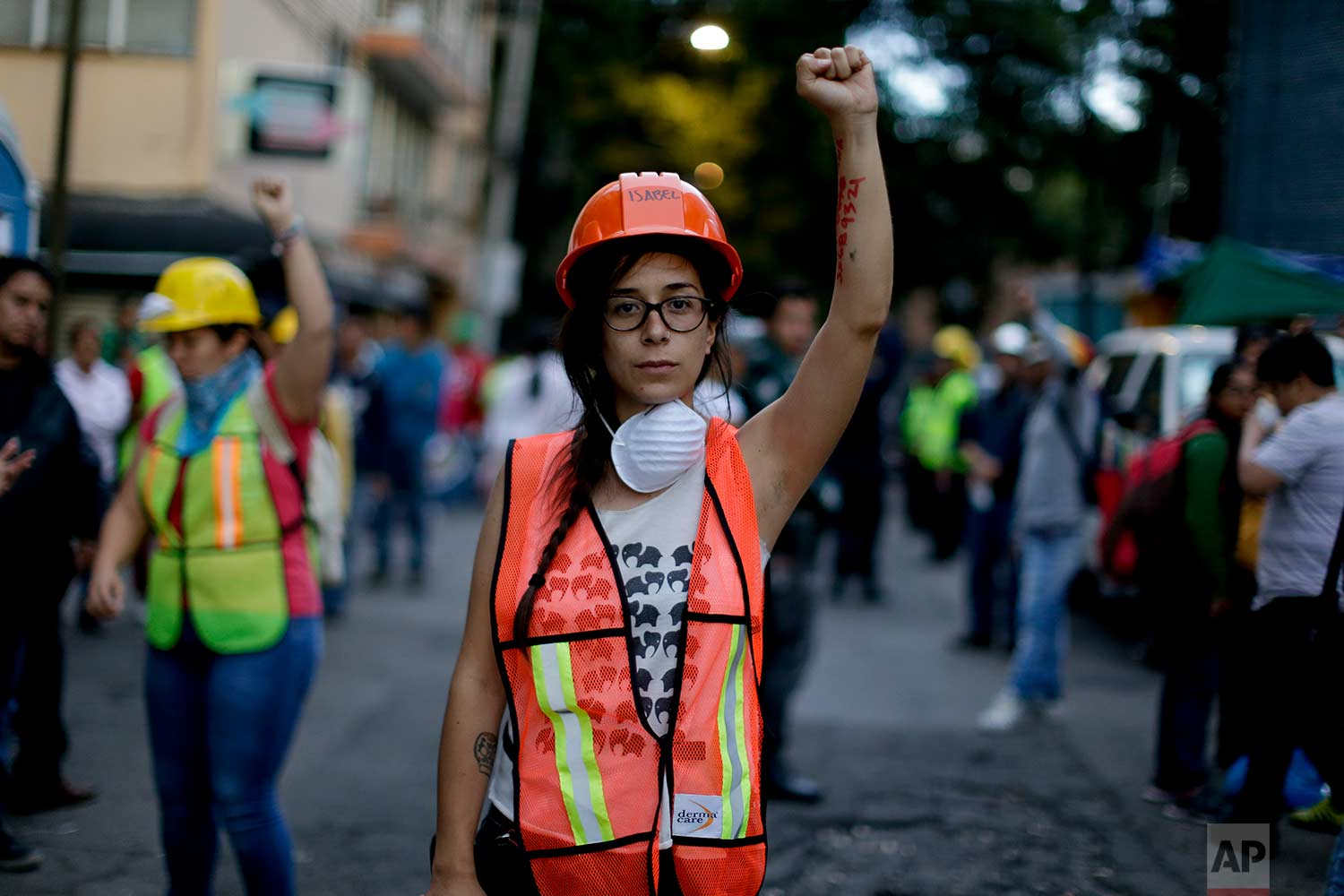 """Isabel Campana, 28, holds up a closed fist as a gesture to maintain silence outside a collapsed building after an earthquake, Sept. 22, 2017,in Mexico City. Campana said she was filming a movie when she and her crew felt the earthquake on Sept. 19, but were not allowed to stop filming and felt conflicted between her job and running to volunteer in the search and rescue efforts. """"I felt impotent when not able to leave immediately to help. It creates a moral conflict. It feels good to know when there are disasters, people come out to help."""" After finishing work, Campana said she started volunteering. (AP Photo/Natacha Pisarenko)"""