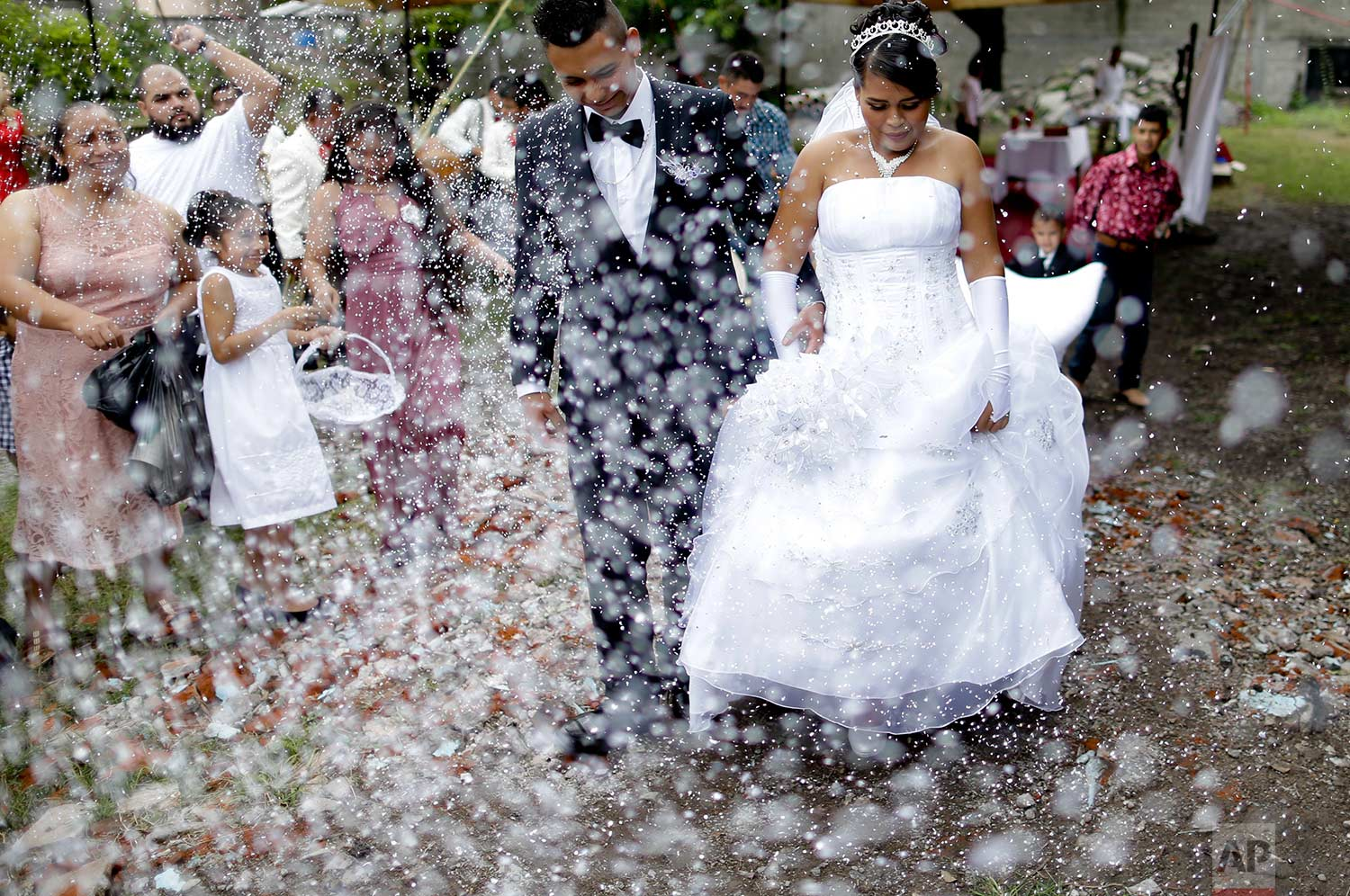 Aremy Sanchez Flores walks with her husband Jose Padilla after getting married in a empty lot in front a church that collapse after an earthquake in Atzala, Mexico, Saturday, Sept. 23, 2017. Eleven people died during a baptism last Tuesday in the Church where the couple had to get married. Flores said she was very sad but is time to move forward. (AP Photo/Natacha Pisarenko)