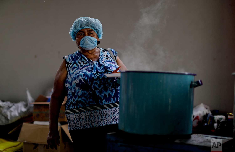Volunteer Abigail Carino Marin cooks for homeless people affected by the earthquake, Sept. 23, 2017, Atzala, Mexico.(AP Photo/Natacha Pisarenko)