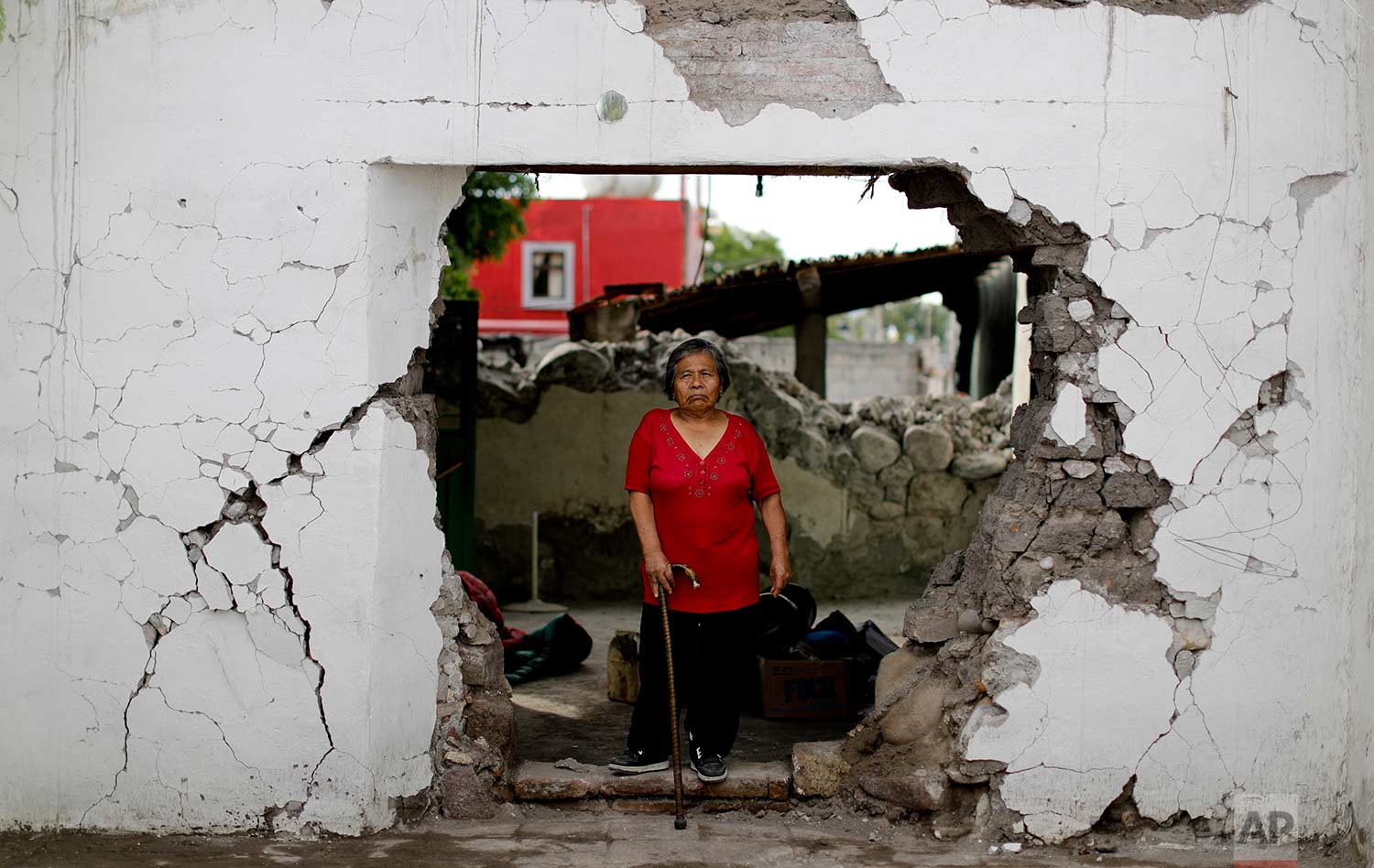 Margarita De La Cruz stands inside her home that was declared condemned after it was damaged by an earthquake,Sept. 23, 2017, Atzala, Mexico. De La Cruz was told by authorities she had to leave her home after the Sept. 19 quake, but the 68-year-old woman said she won't leave because she has spent her entire life there, and has moved into a tiny room that works as a kitchen in the garden. (AP Photo/Natacha Pisarenko)