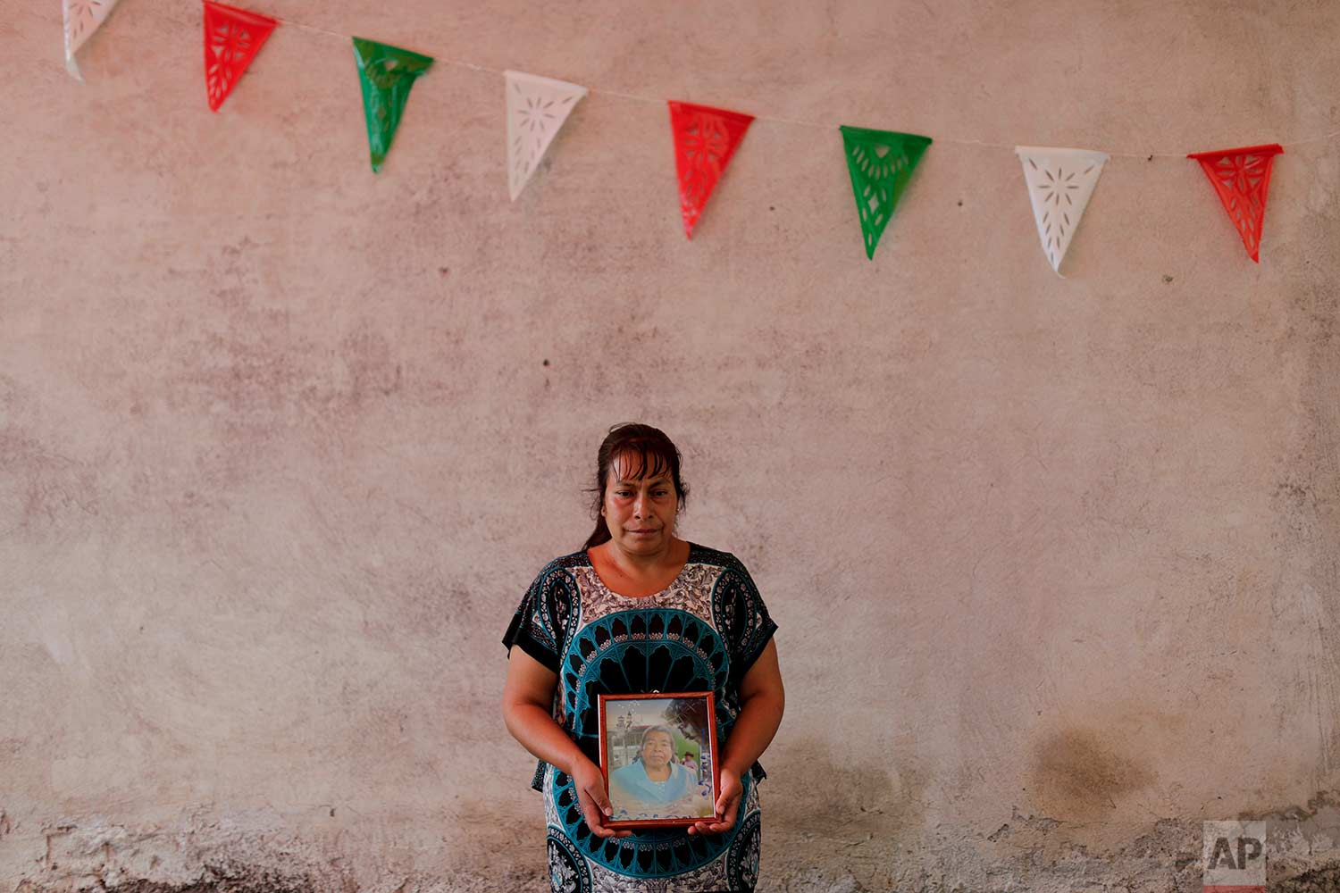 """Juana Villanueva, 41, holds the photo of her mother Carmela Meresis, who died in a church that collapsed during the Sept. 19 earthquake, Sept. 23, 2017, in Atzala, Mexico. Villanueva lost her two sisters, a brother-in-law, a nephew and a niece to the quake who were attending a baptism when the temple collapsed. Villanueva said: """"We need to have the will because God left us here to live. We're alive for a reason, to rise above all else and support each other. This is really hard what we're dealing with, but if we don't give it all we've got and find strength and courage from where we can, who will? If we don't help each other spiritually and emotionally, we'll fall. No, we have to have the will because life goes on."""" (AP Photo/Natacha Pisarenko)"""