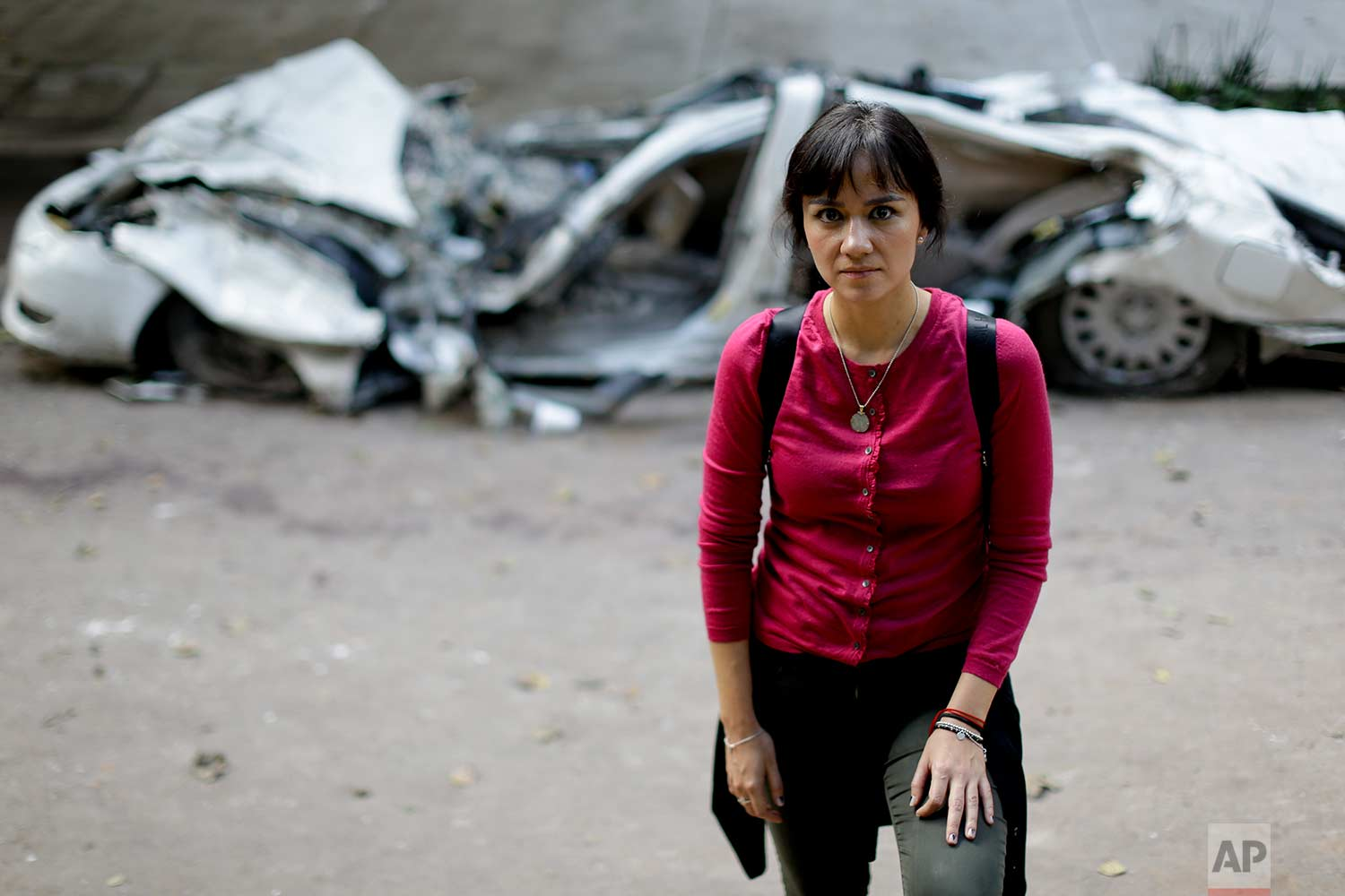 """Mariana Mancera, a 35-year-old makeup artist, poses for a portrait in front of an earthquake-crushed car, In this Friday, Sept. 22, 2017 photo, in Mexico City. Mancera, whose family owns a restaurant, said she volunteered to provide food to those searching for survivors in the rubble after the 7.1 earthquake on Sept. 19. """"If I cannot work removing stones and debris, then I'll do something else to give them energy so they can do their jobs."""" (AP Photo/Natacha Pisarenko)"""
