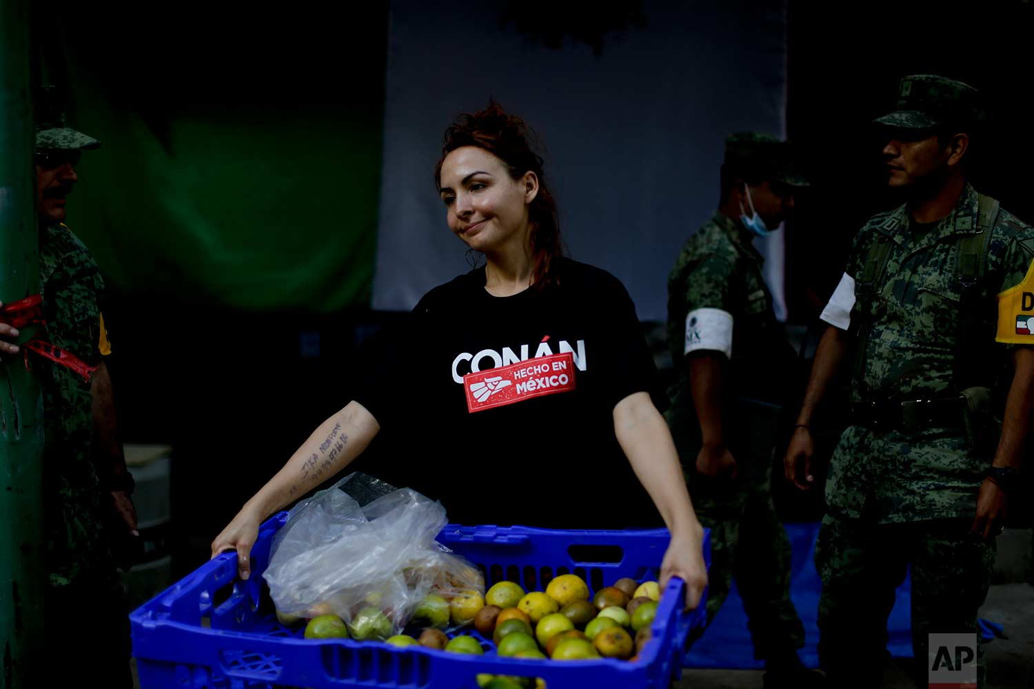 """Ilya Monforte, a 40-year-old makeup artist, carries oranges for search and rescue workers at a building that collapsed from an earthquake,Sept. 22, 2017 photo,in Mexico City. Monforte, a volunteer in charge of feeding the search and rescue team and military police at the sight following the Sept. 19 magnitude 7.1 earthquake, said: """"For the last three days we did not need money, it was like living in socialism. The collective goal during these days was to help others, to take care of them, love them. On each corner you can find people giving."""" (AP Photo/Natacha Pisarenko)"""