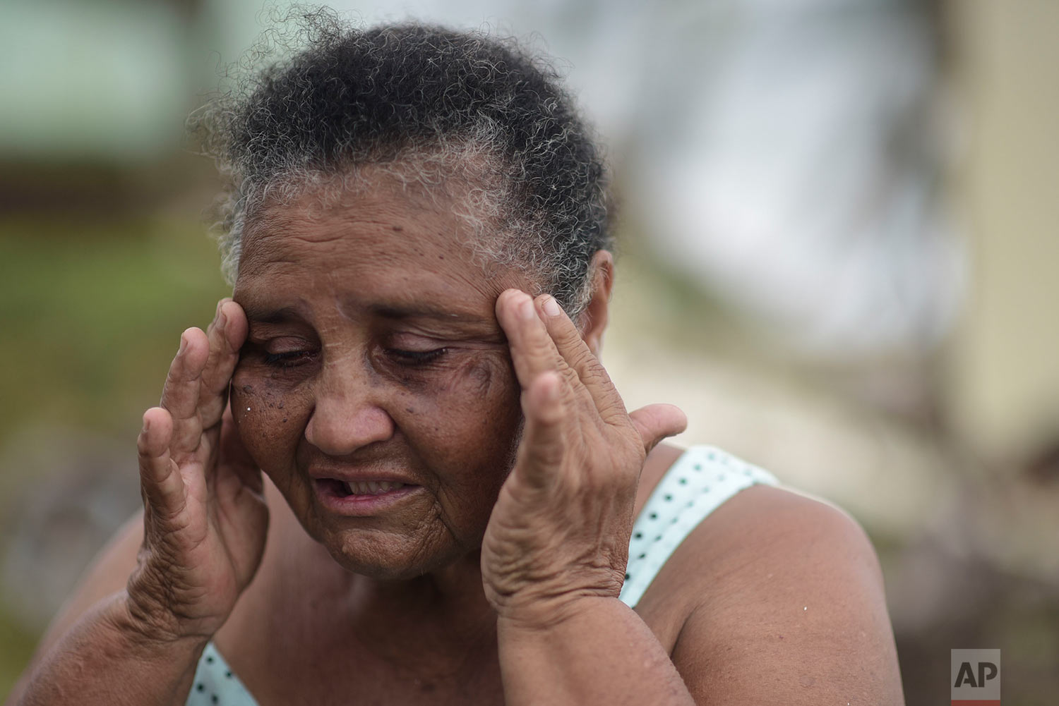 El Negro community resident Irma Torres Rodriguez tries to stay calm after loosing a portion of her roof to the fury of Hurricane Maria, in Puerto Rico, Thursday, September 21, 2017.(AP Photo/Carlos Giusti)