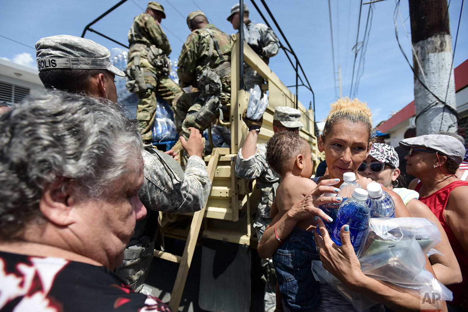 National Guard Soldiers arrive at Barrio Obrero in Santurce to distribute water and food among those affected by the passage of Hurricane Maria, in San Juan, Puerto Rico, Sunday, Sept. 24, 2017. (AP Photo/Carlos Giusti)