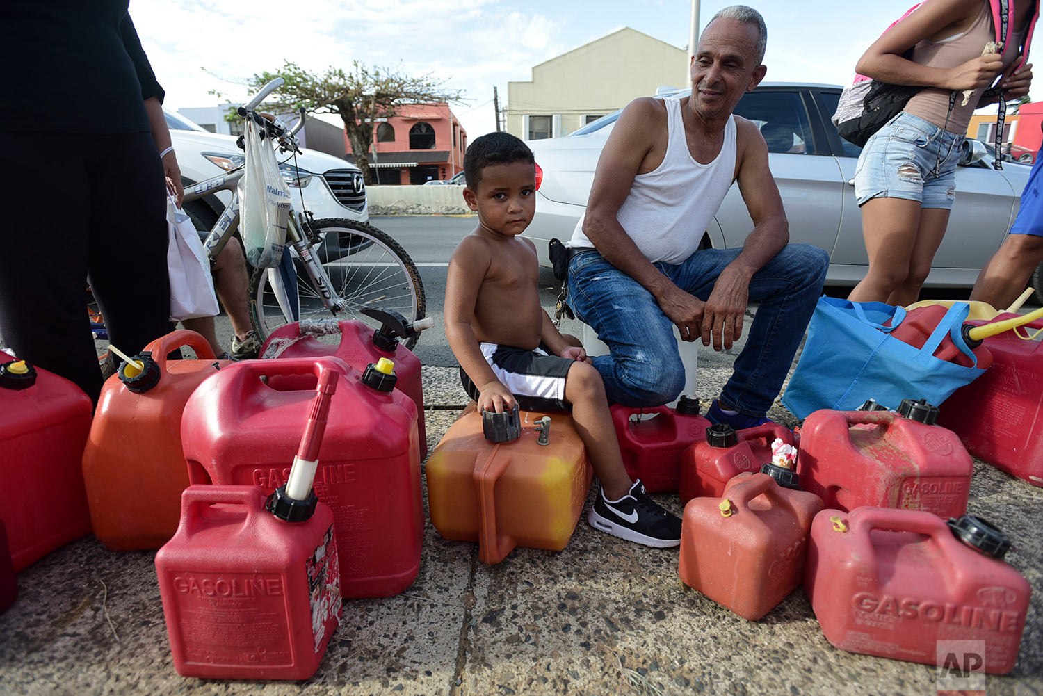 Ricardo Gonzalez sits on a gas container with his uncle Miguel Colon as hundreds of people wait in line since early morning hours to buy gasoline three days after the impact of Hurricane Maria in Carolina, Puerto Rico, Saturday, Sept. 23, 2017. (AP Photo/Carlos Giusti)